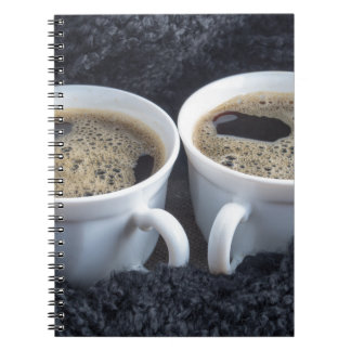 Two white cups with black coffee and foam note book