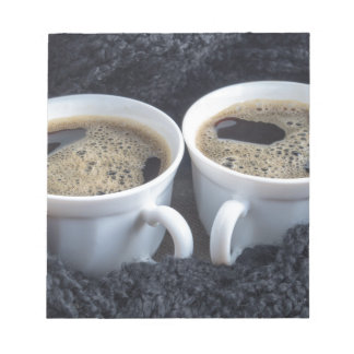 Two white cups with black coffee and foam notepad