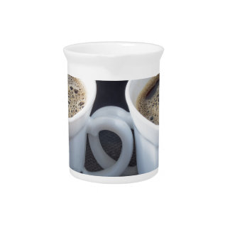 Two white cups with black coffee and foam pitcher