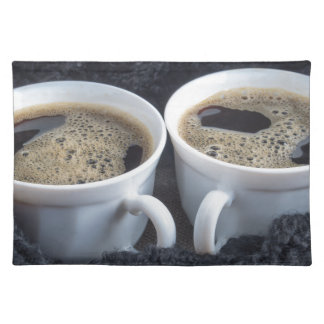 Two white cups with black coffee and foam placemat