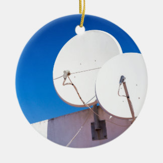Two white satellite dishes on house wall ceramic ornament