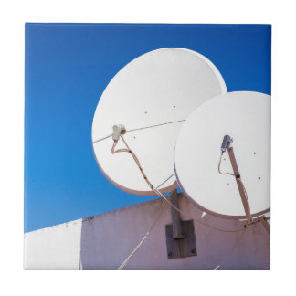 Two white satellite dishes on house wall ceramic tile