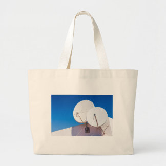 Two white satellite dishes on house wall large tote bag