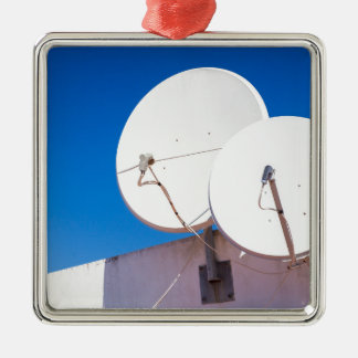 Two white satellite dishes on house wall metal ornament
