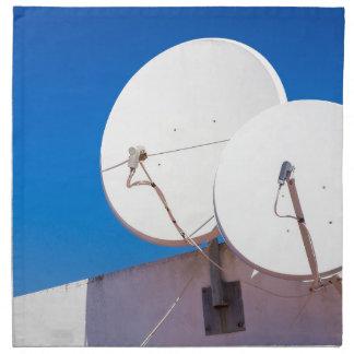 Two white satellite dishes on house wall napkin
