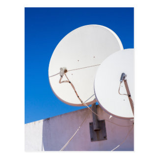 Two white satellite dishes on house wall postcard
