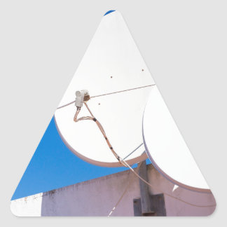 Two white satellite dishes on house wall triangle sticker