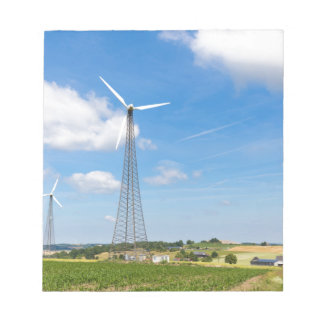 Two windmills in rural area with blue sky notepad