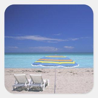 Umbrella and two lounge chairs on beach, Miami Square Sticker