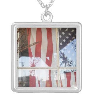 USA, Oregon, Shaniko. Flag in window next to Square Pendant Necklace