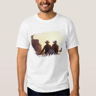 USA, Wyoming, Pine Bluffs. Two men shake Tshirts