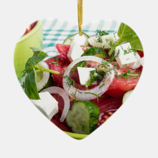 Useful vegetarian salad with raw tomatoes ceramic heart decoration