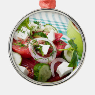 Useful vegetarian salad with raw tomatoes Silver-Colored round decoration
