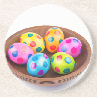 Various painted chicken easter eggs in wooden bowl coaster