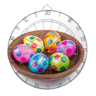 Various painted chicken easter eggs in wooden bowl dartboard