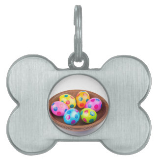 Various painted chicken easter eggs in wooden bowl pet name tag