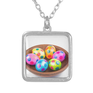 Various painted chicken easter eggs in wooden bowl silver plated necklace