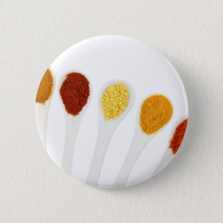 Various seasoning spices on porcelain spoons 6 cm round badge