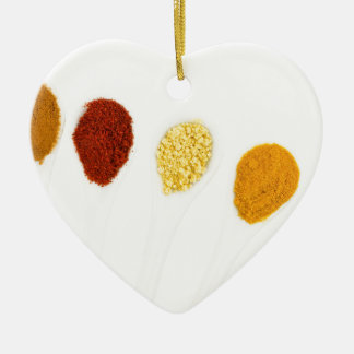 Various seasoning spices on porcelain spoons ceramic heart decoration