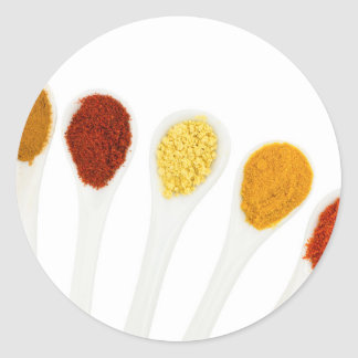 Various seasoning spices on porcelain spoons classic round sticker