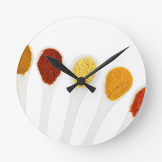 Various seasoning spices on porcelain spoons round clock