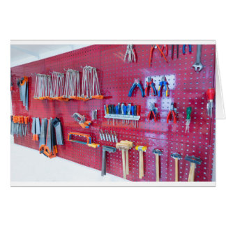 Various tools hanging at wall in high school card