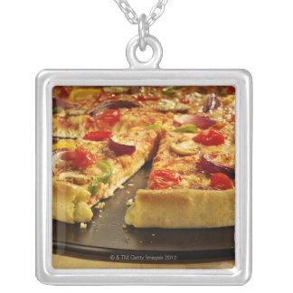 Vegetable pizza sliced on black pan on wood necklace