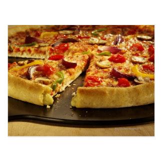Vegetable pizza sliced on black pan on wood postcard