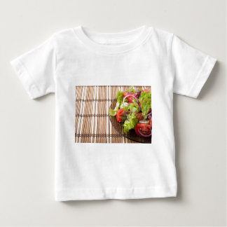 Vegetarian salad from fresh vegetables on a bamboo baby T-Shirt