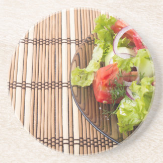 Vegetarian salad from fresh vegetables on a bamboo coaster