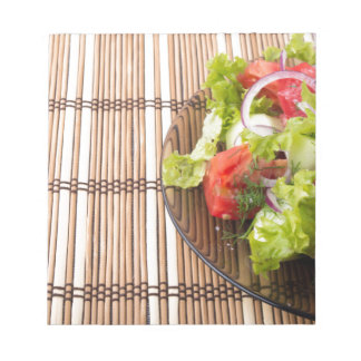Vegetarian salad from fresh vegetables on a bamboo notepad