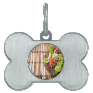 Vegetarian salad from fresh vegetables on a bamboo pet name tags