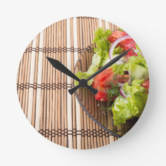 Vegetarian salad from fresh vegetables on a bamboo round clock