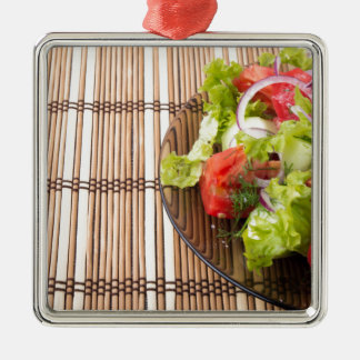 Vegetarian salad from fresh vegetables on a bamboo Silver-Colored square decoration