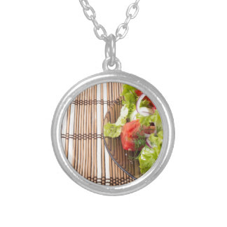 Vegetarian salad from fresh vegetables on a bamboo silver plated necklace