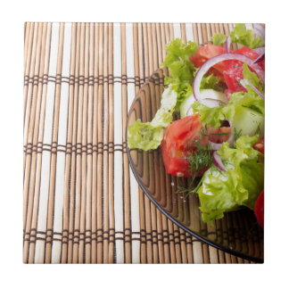 Vegetarian salad from fresh vegetables on a bamboo small square tile