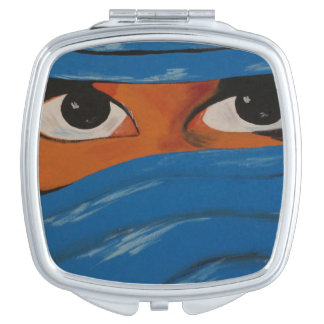 Veiled woman into blue travel mirror