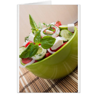 Vertical view close-up on a green bowl with salad card
