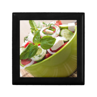 Vertical view close-up on a green bowl with salad small square gift box