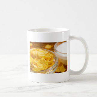 View close-up of milk and a glass bowl of flakes coffee mug