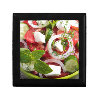 View close-up on a green bowl with a salad small square gift box