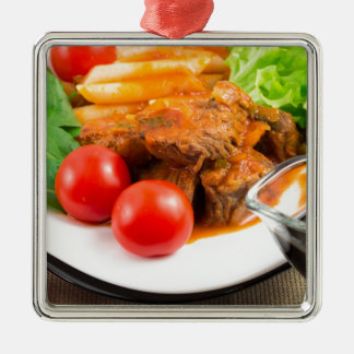 View close-up on a meal of beef stew with pasta metal ornament