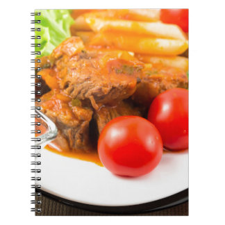 View close-up on a meal of beef stew with pasta spiral note books
