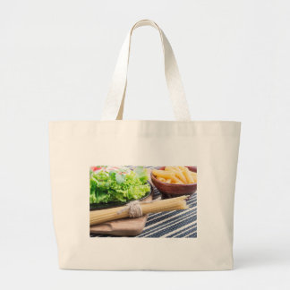 View close-up on uncooked pasta and spaghetti large tote bag