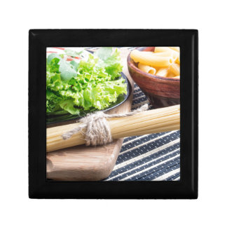 View close-up on uncooked pasta and spaghetti small square gift box