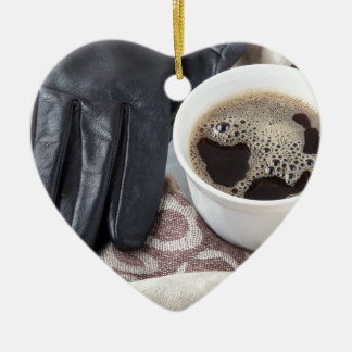 View close-up on white cup of coffee and gloves ceramic ornament