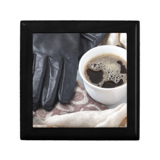 View close-up on white cup of coffee and gloves gift box