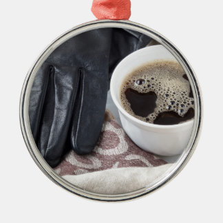 View close-up on white cup of coffee and gloves metal ornament