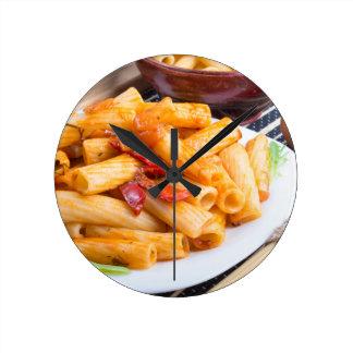 View closeup on a dish of rigatoni pasta round clock