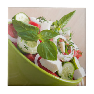 View closeup on a green bowl with a useful salad small square tile